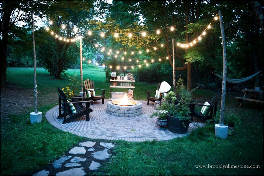 An outdoor patio with a firepit at dusk