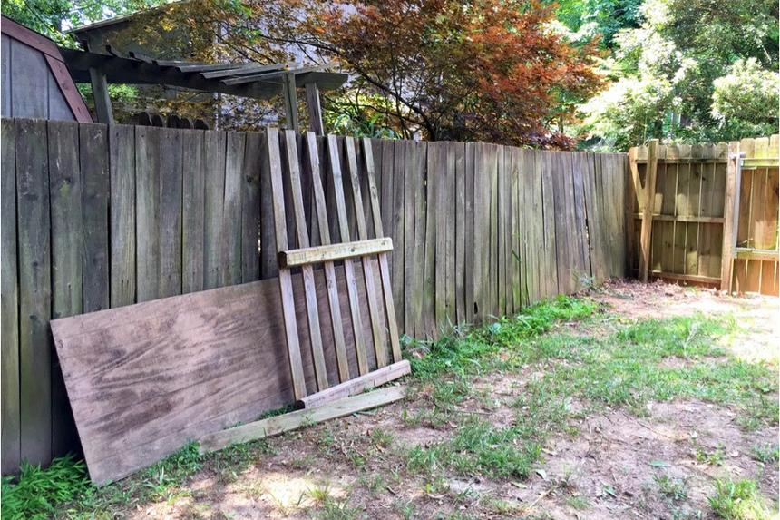 An old, mossy wood fence with patchy grass