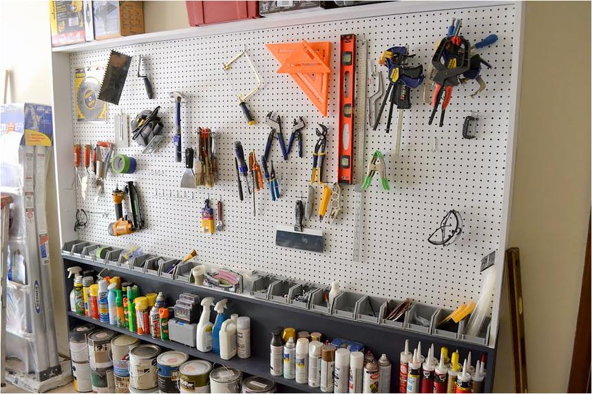 A white pegboard with tools in a garage