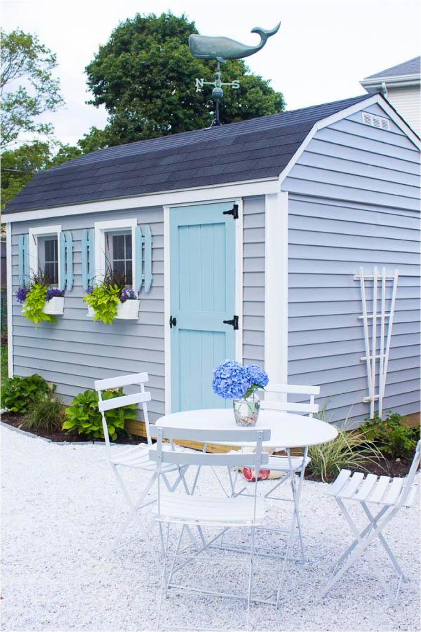A blue outdoor shed with a whale weather vane & white table