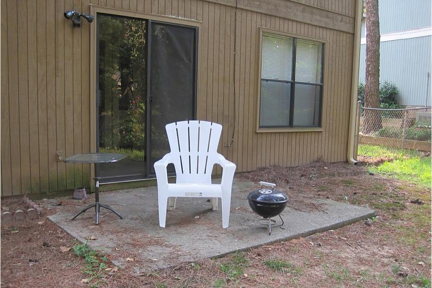 A concrete slab outside a sliding door with a white chair