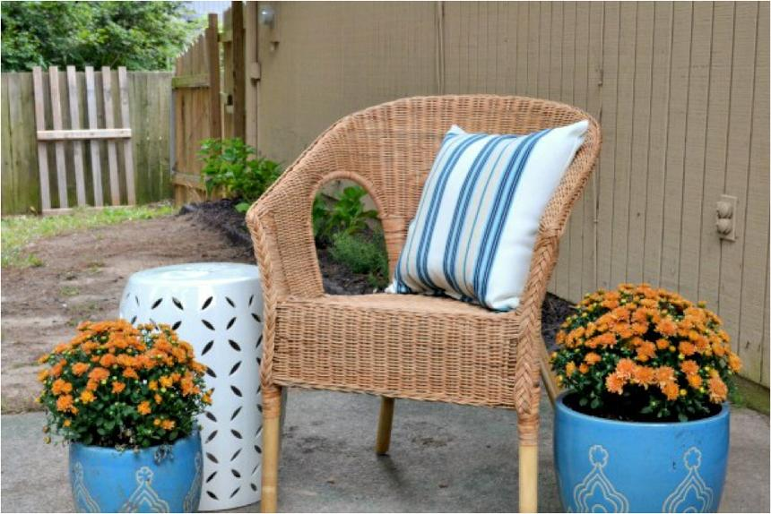A wicker chair on a concrete slab with two blue pots