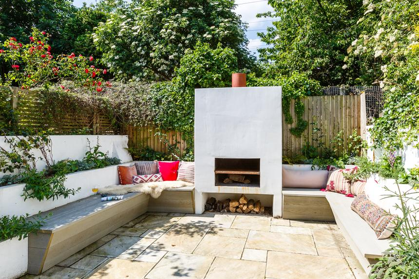 An outdoor fireplace with wood bench seating on a patio