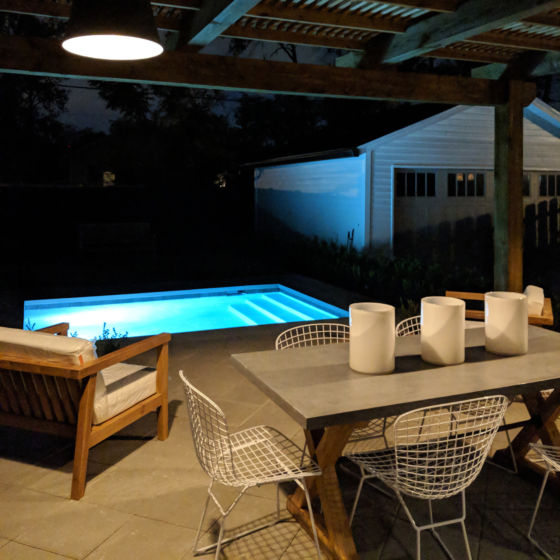A backyard with pool and covered patio at night