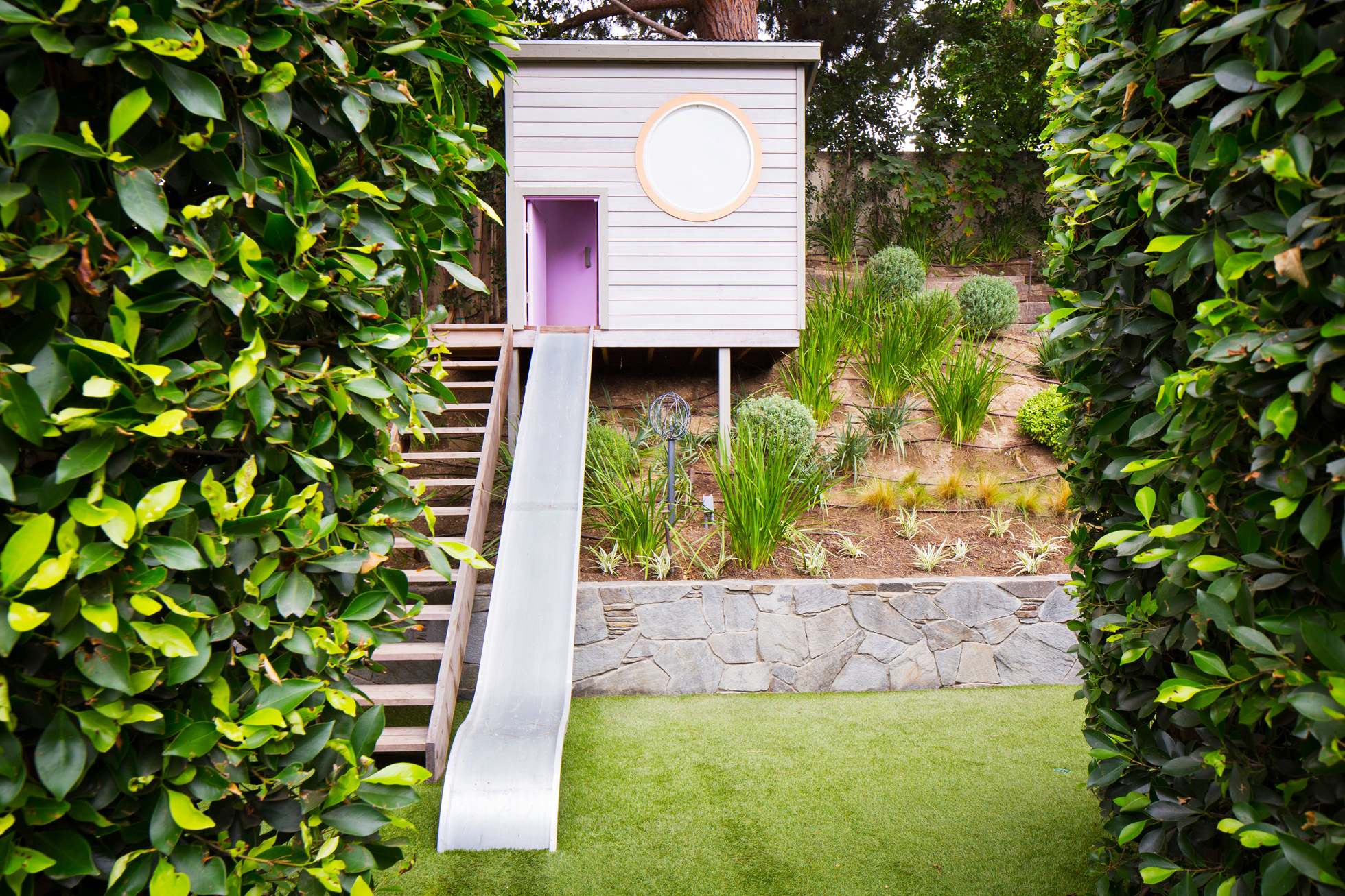 A modern treehouse with a purple slide