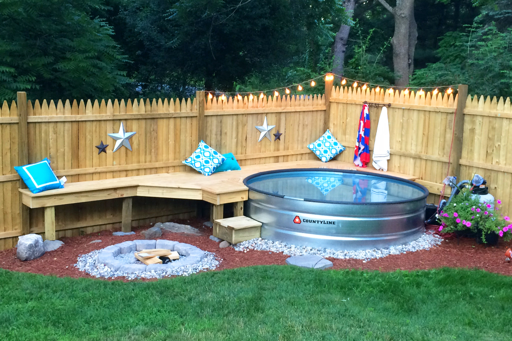 A stock tank pool and a fire pit with seating in a backyard