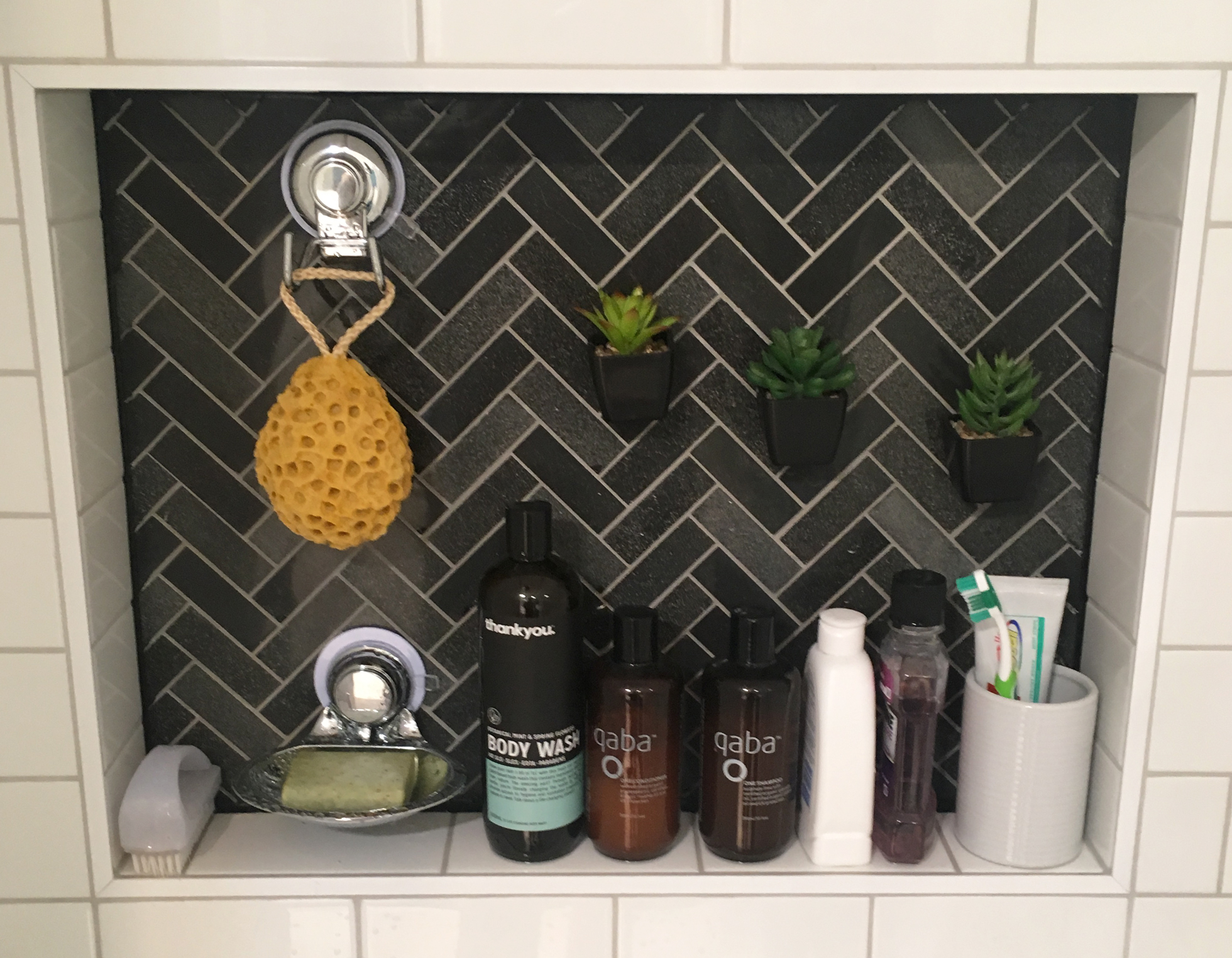 A black tiled built-in shelf in a white tiled shower