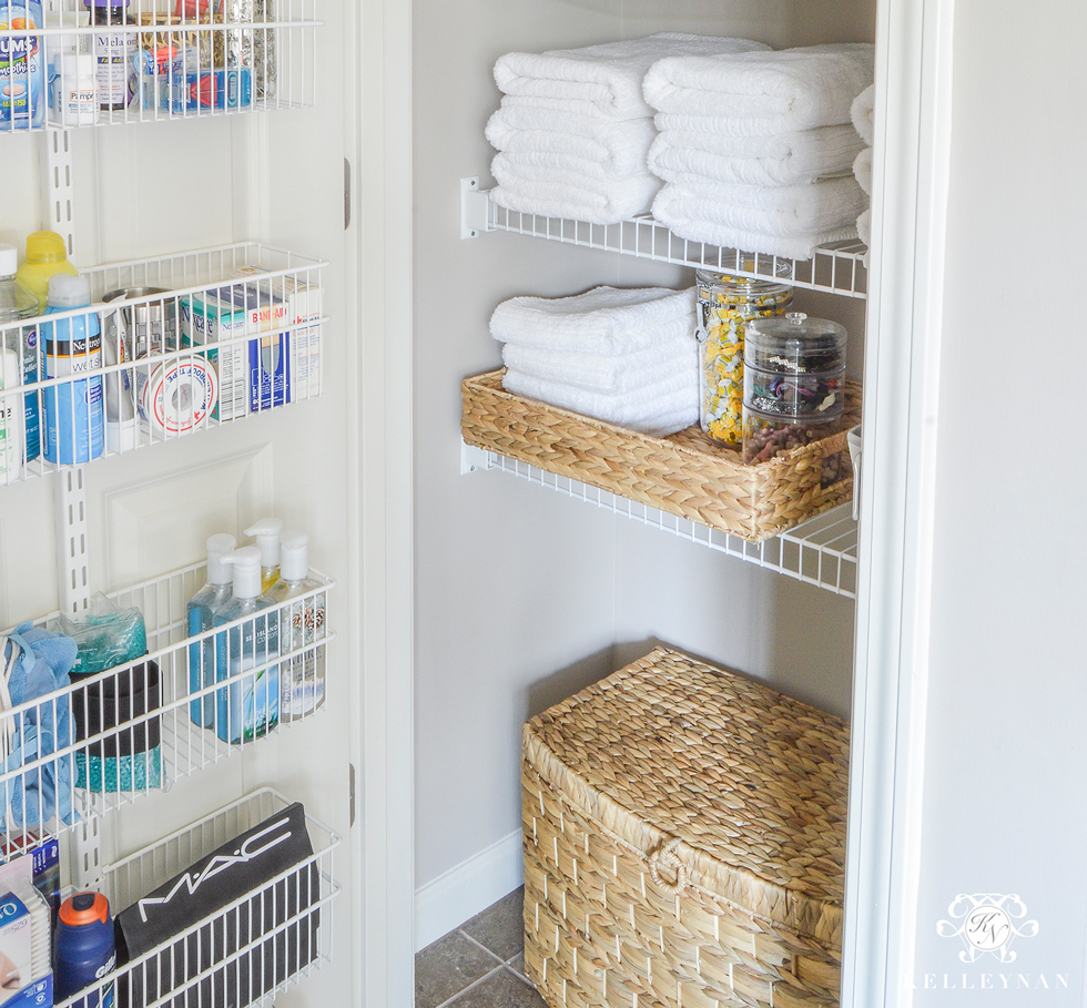 A linen closet filled with towels and a wire rack on door