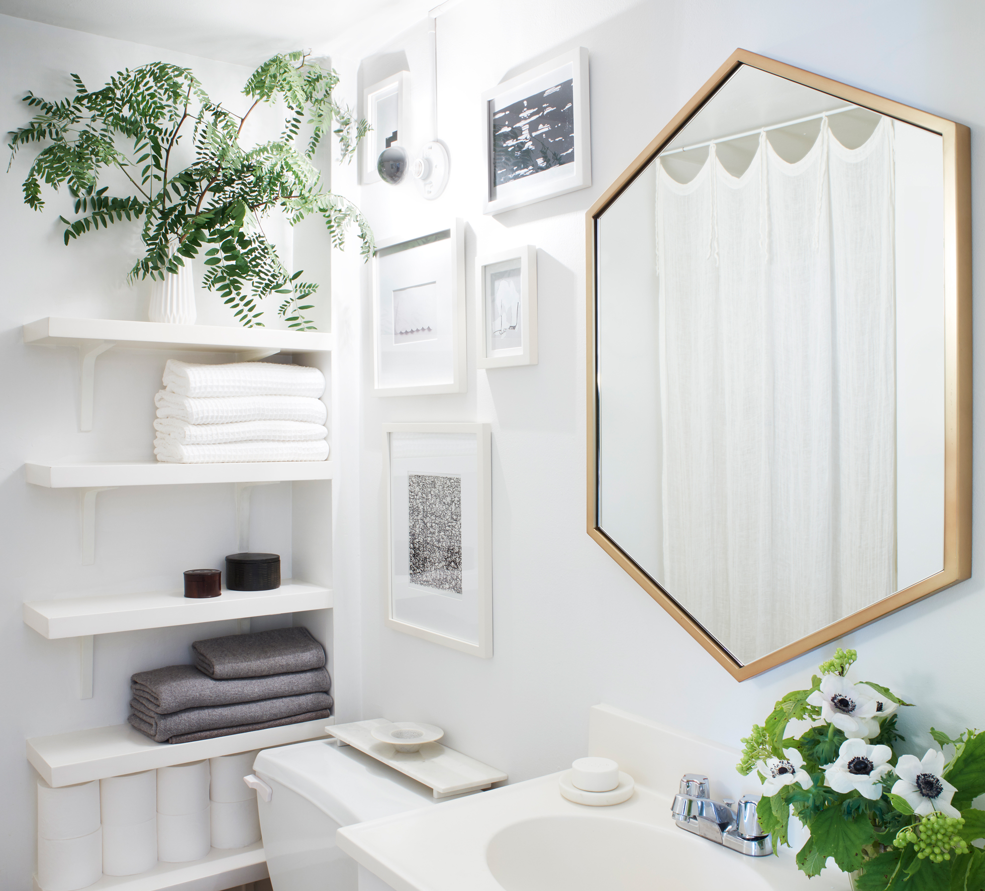 A bright white bathroom with open shelving