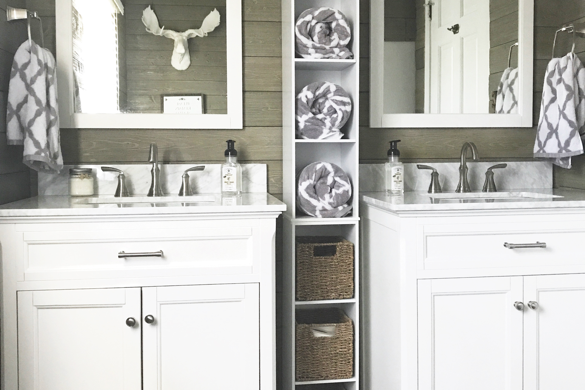 Two sinks in a shiplap bathroom with shelving between
