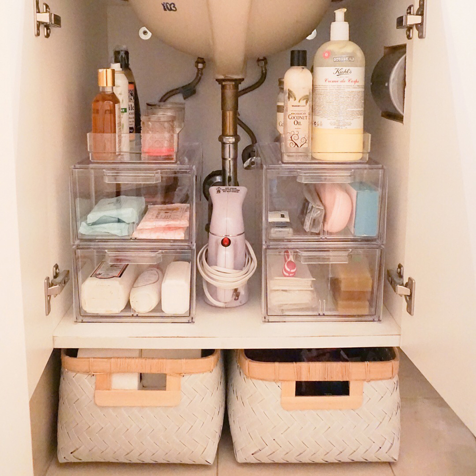 Clear organizers with toiletries under a bathroom sink