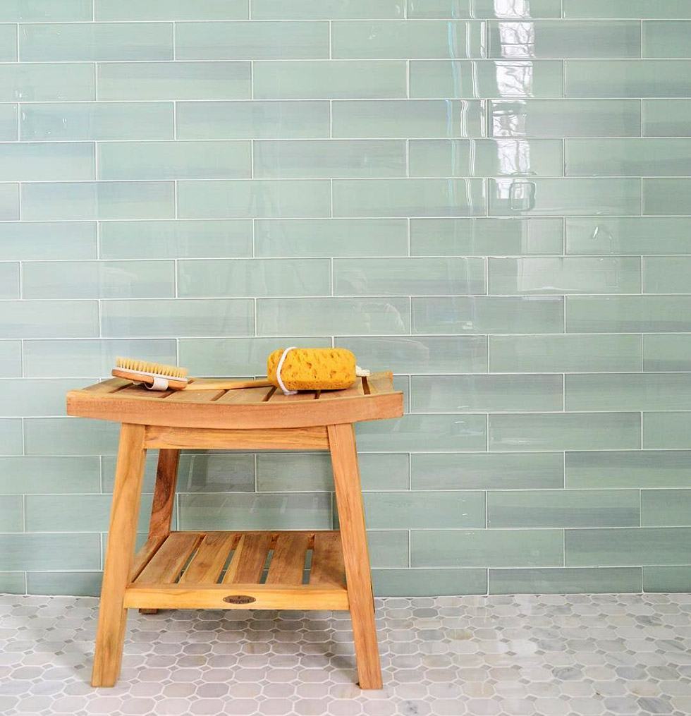 Natural wood bathroom stool before wall of green glass tiles