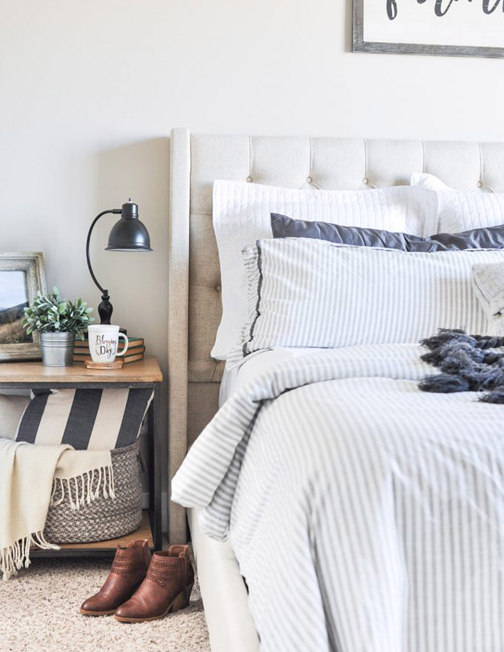 Bed with blue and white striped comforter & padded bed frame
