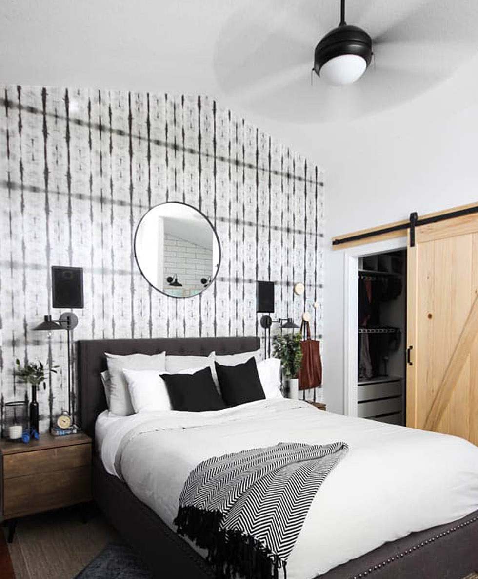 Black and white bedroom with natural accents and ceiling fan