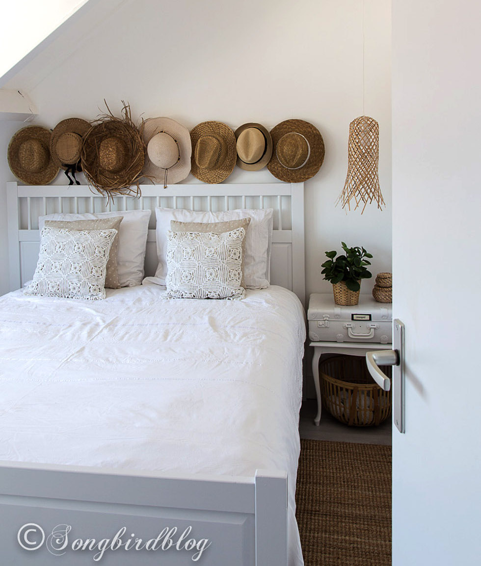 White bed with assortment of straw and cowboy hats above it