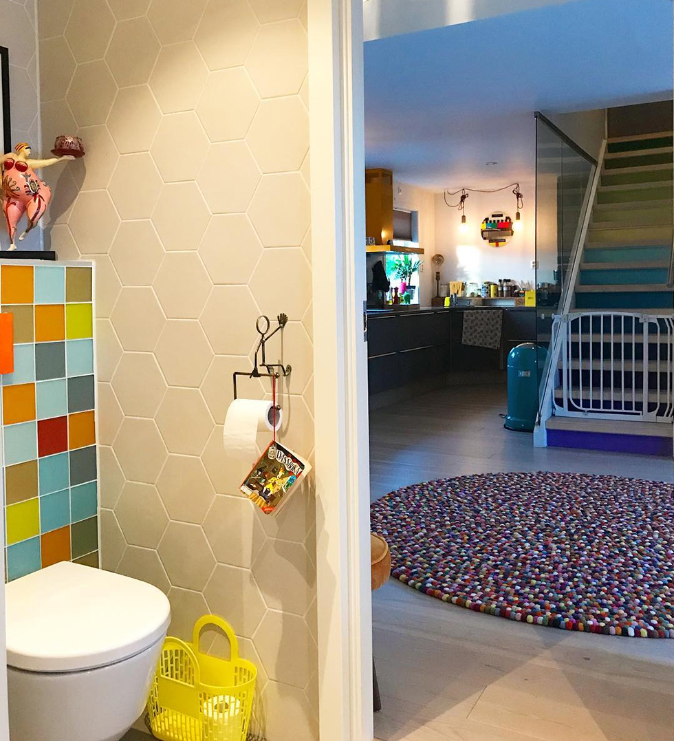 Bathroom with colorful tile showing glimpse of gum ball rug