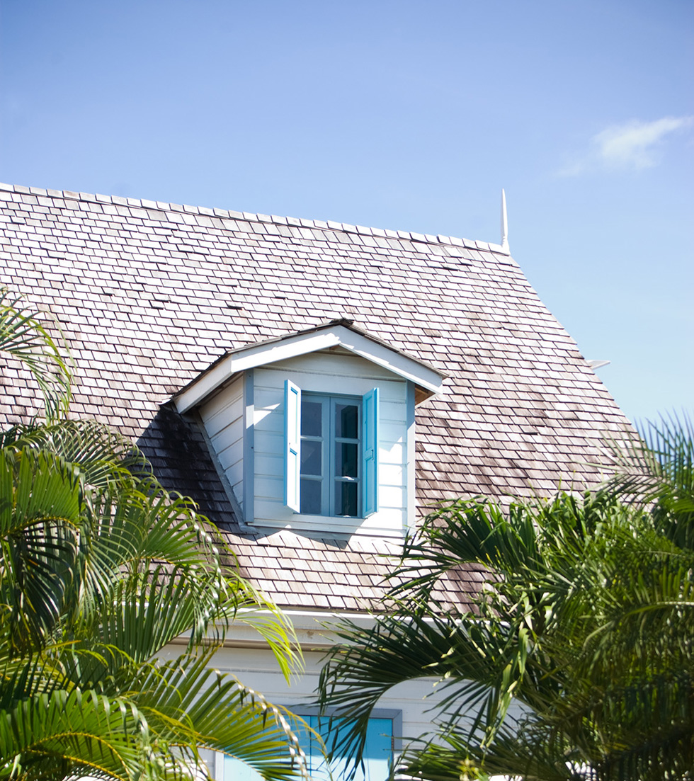 Roof on a white house against a blue sky in a tropical area