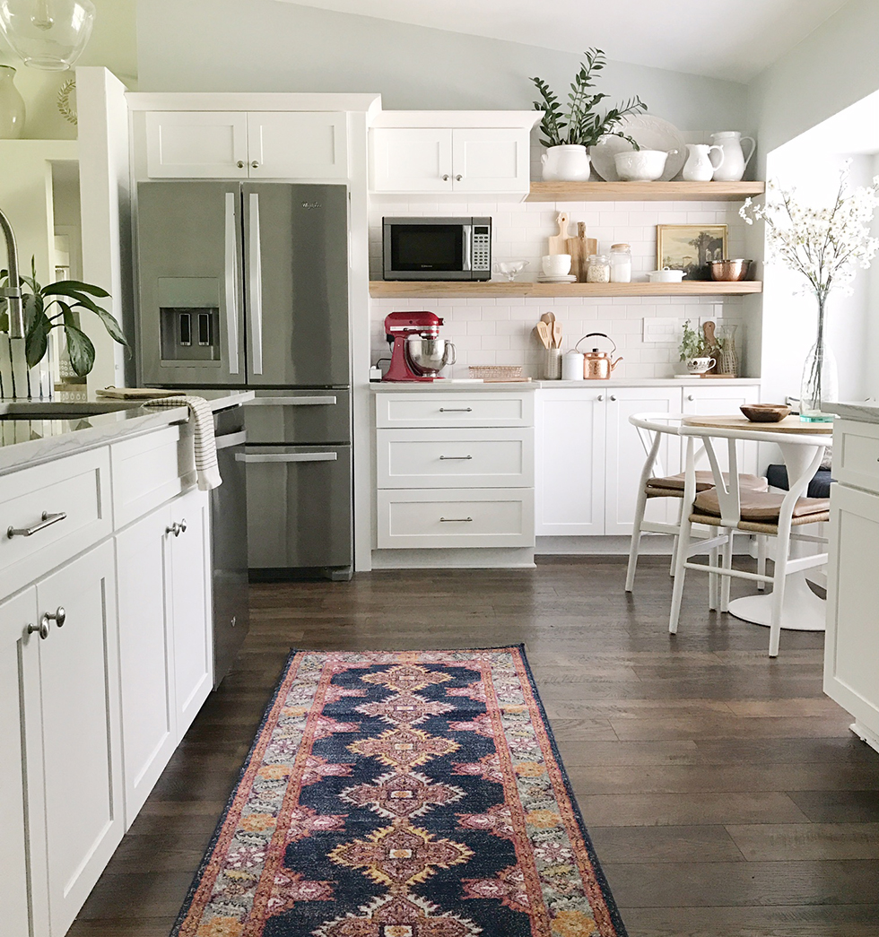 All-white kitchen with dark wood floors and red and blue rug