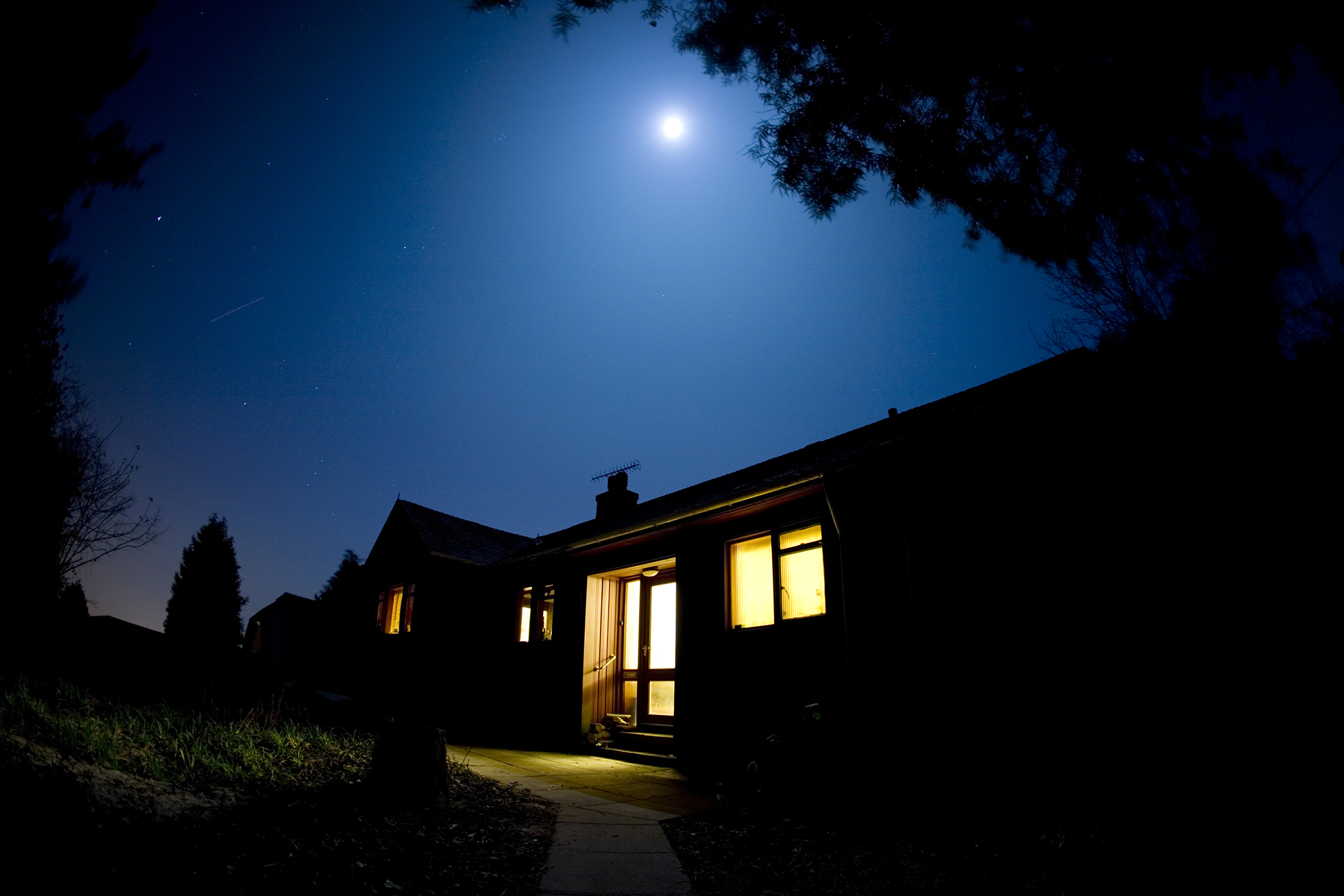 Silhouette of home at night | Stop watering lawns in morning