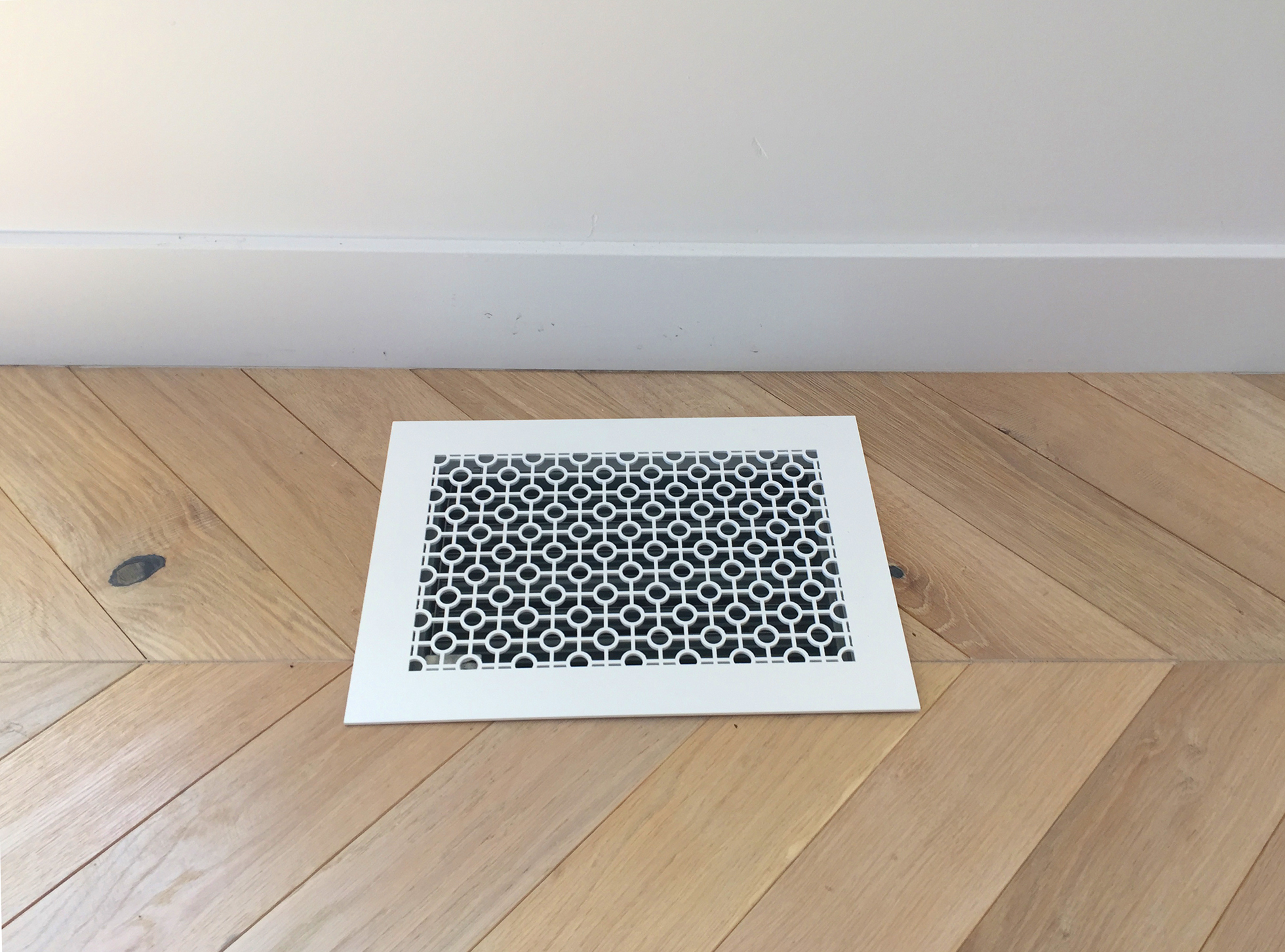 White metal floor vent in herringbone wood floor