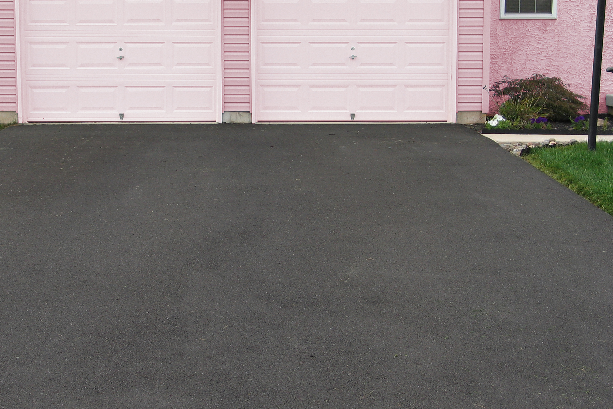 Sealed asphalt driveway at pink house