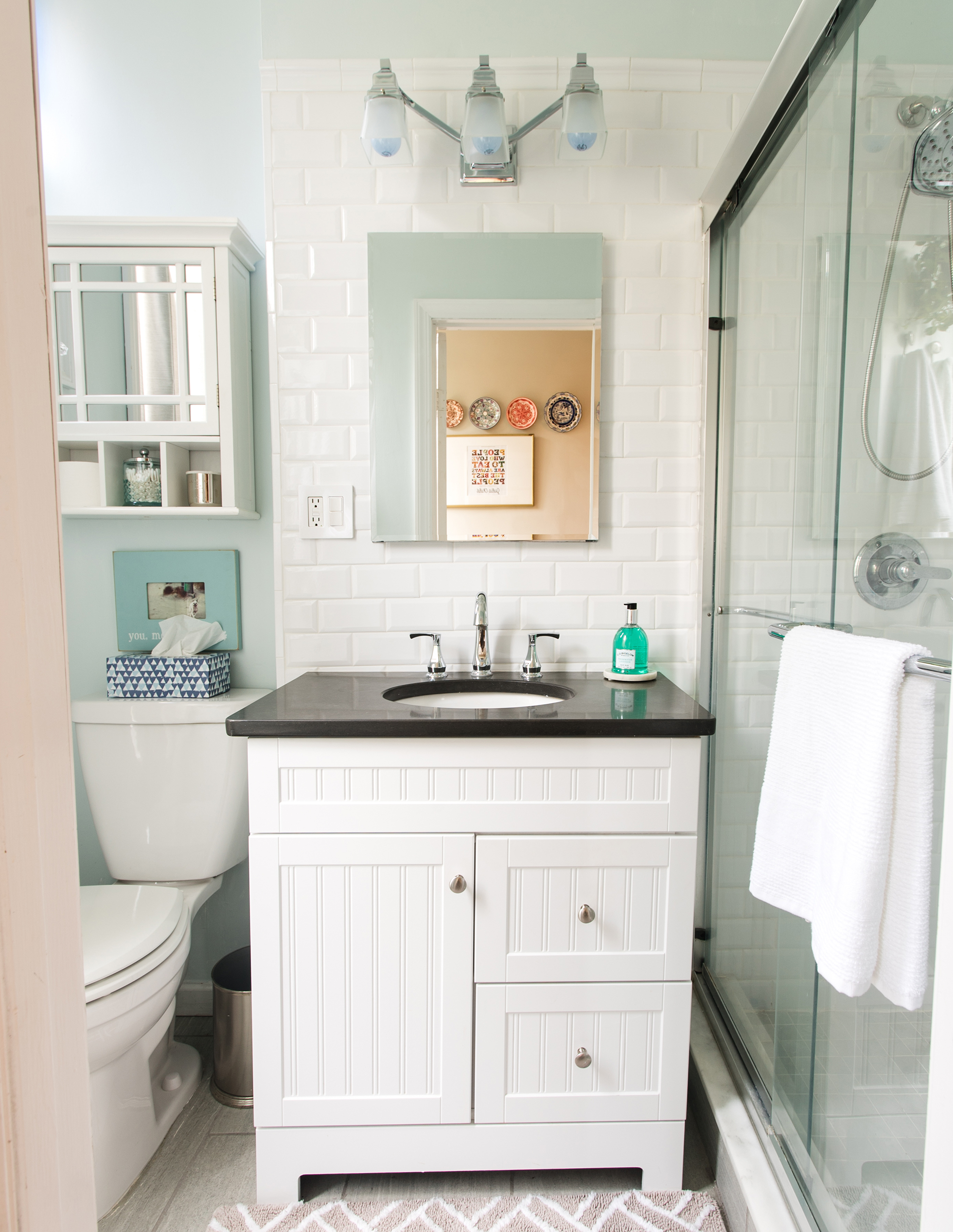 White bathroom with black-counter vanity and glass shower