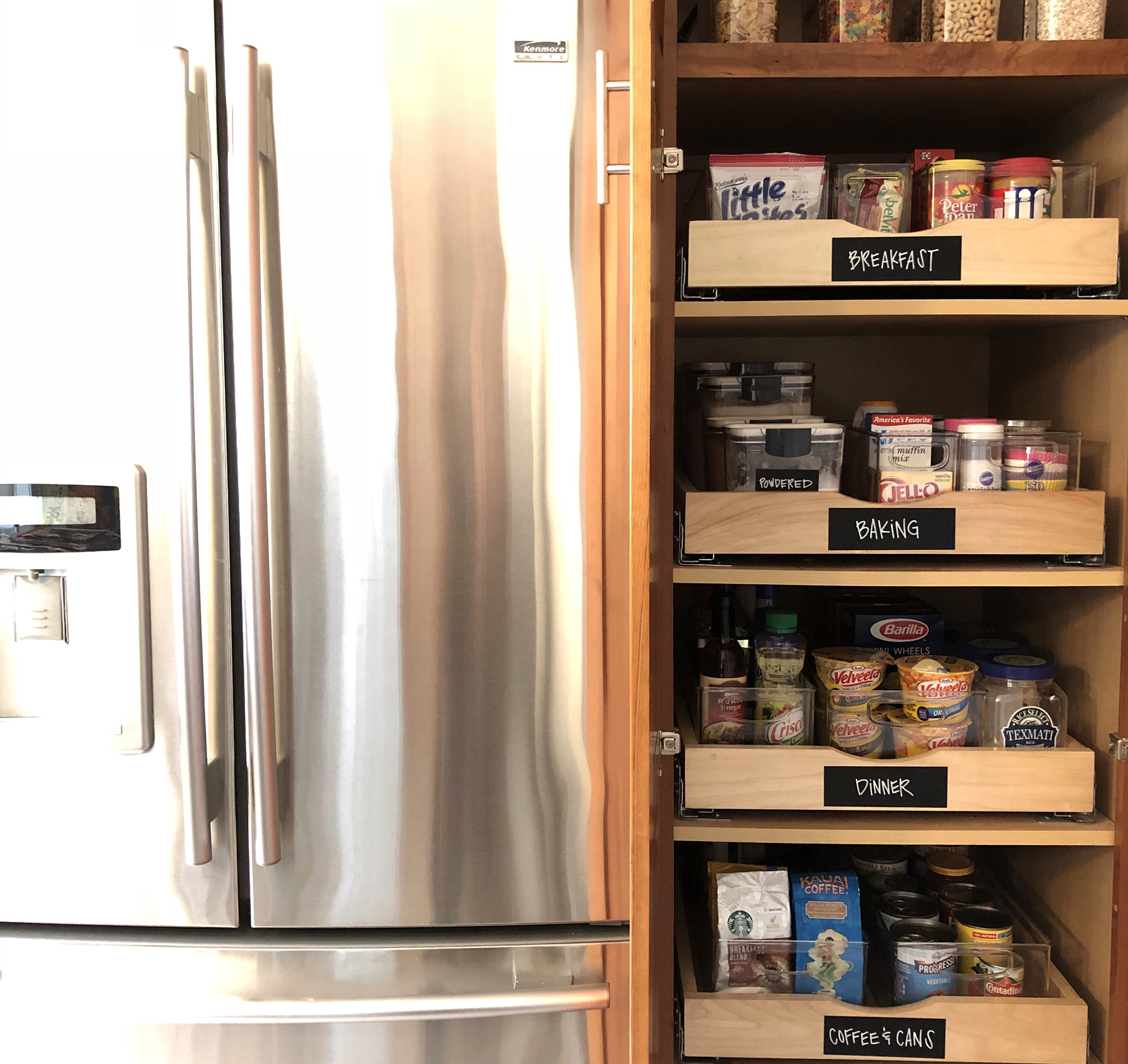 Stainless steel fridge beside cupboard with roll out drawers