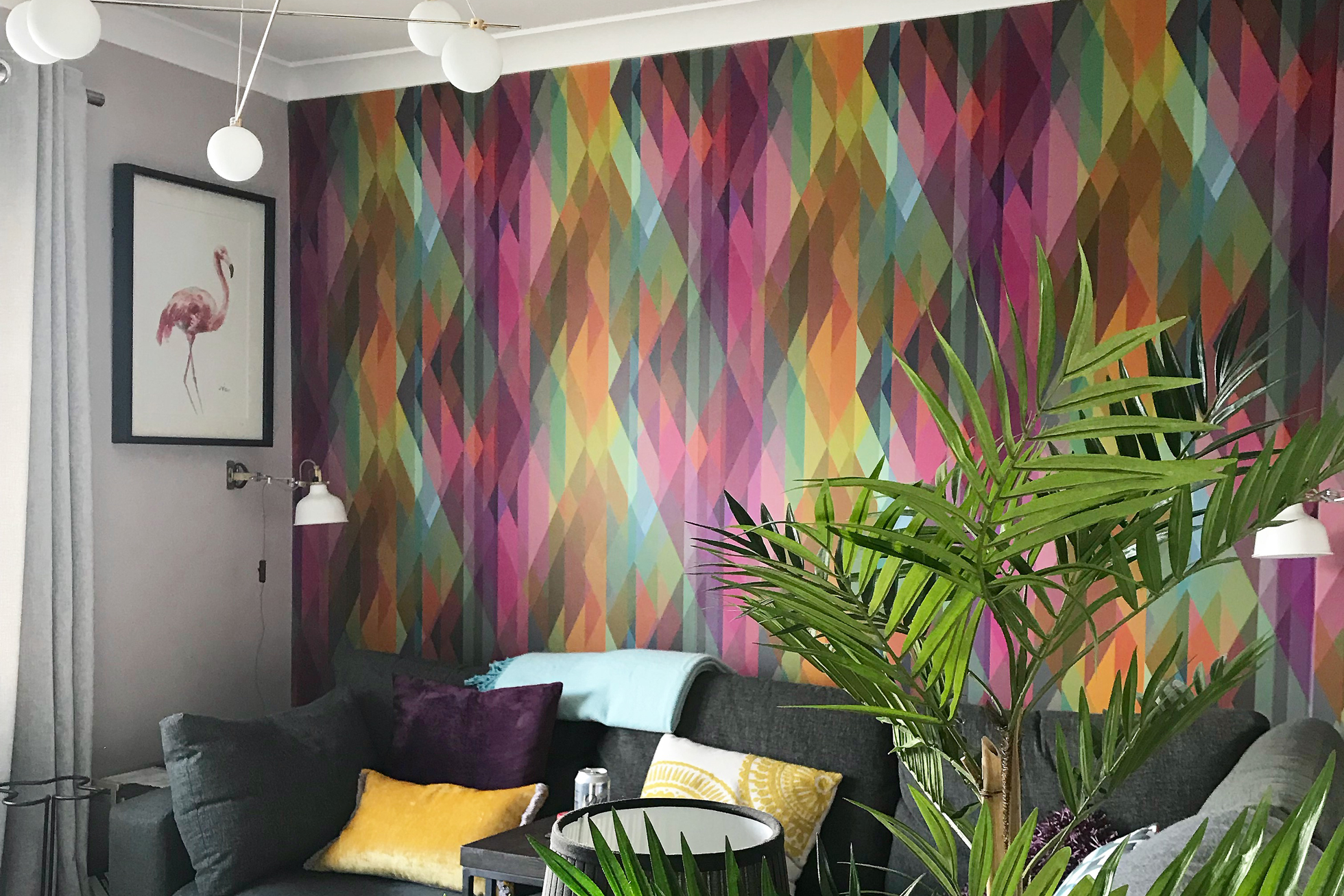 A wall in a living room covered in multi-colored wallpaper