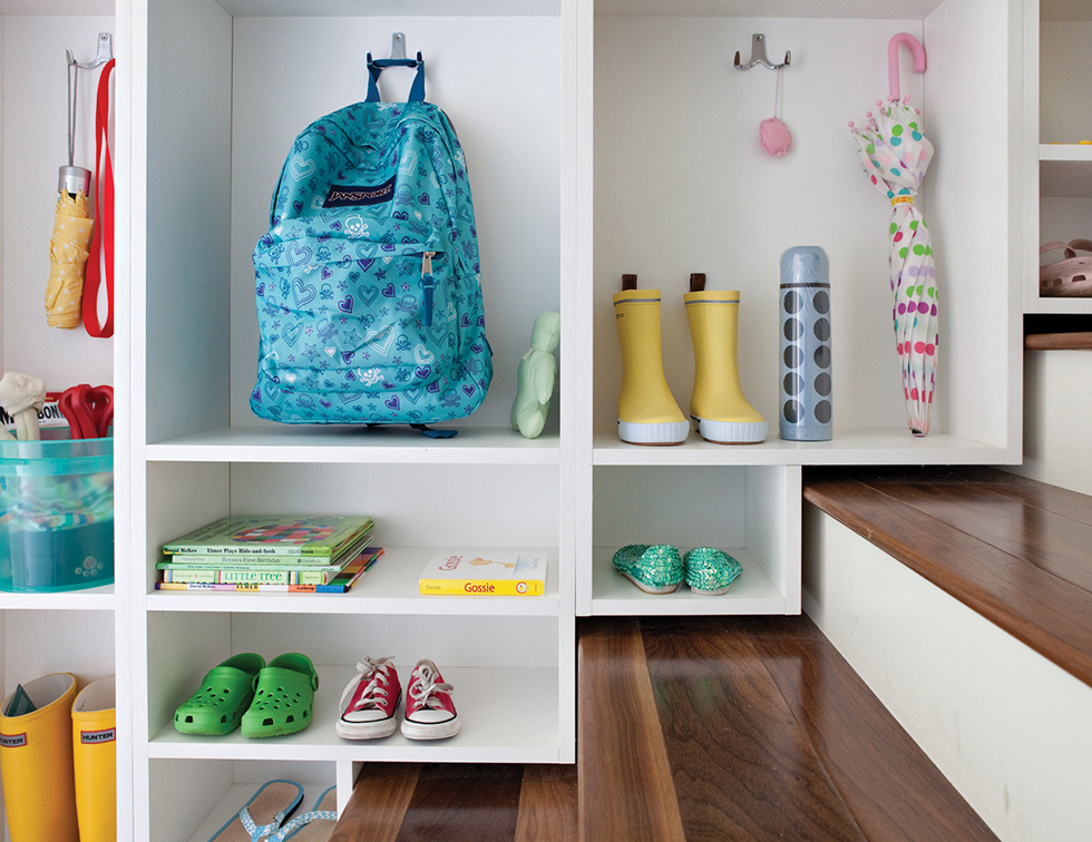 Mudroom storage built into staircase with bright items