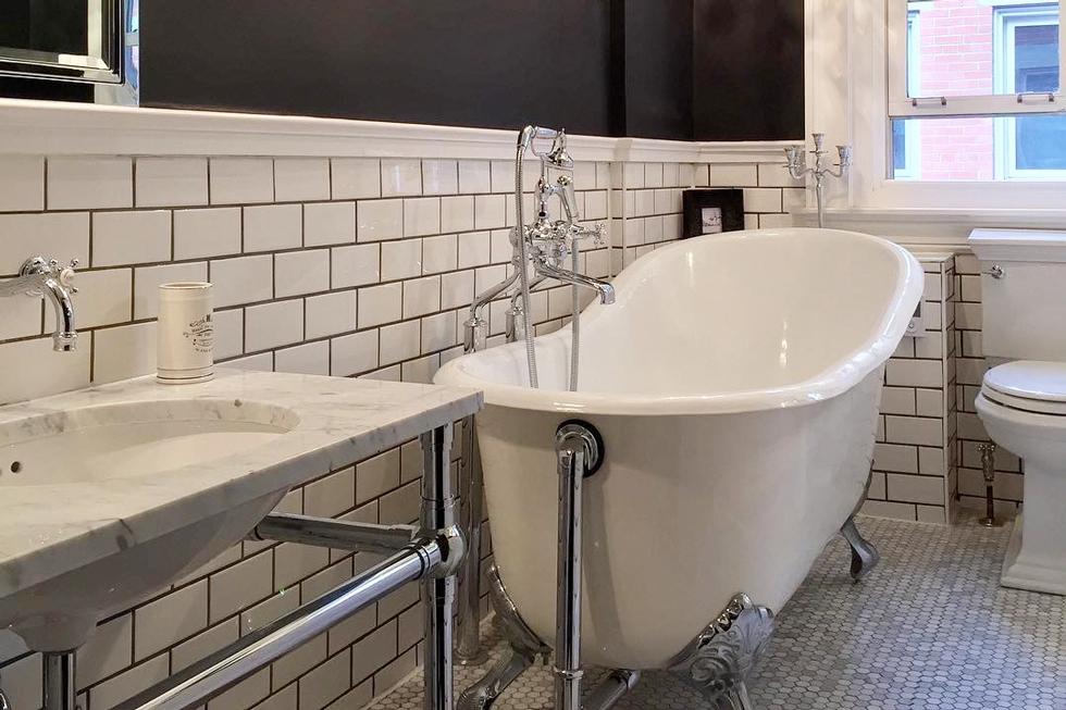A white clawfoot tub in a restored tiled bathroom