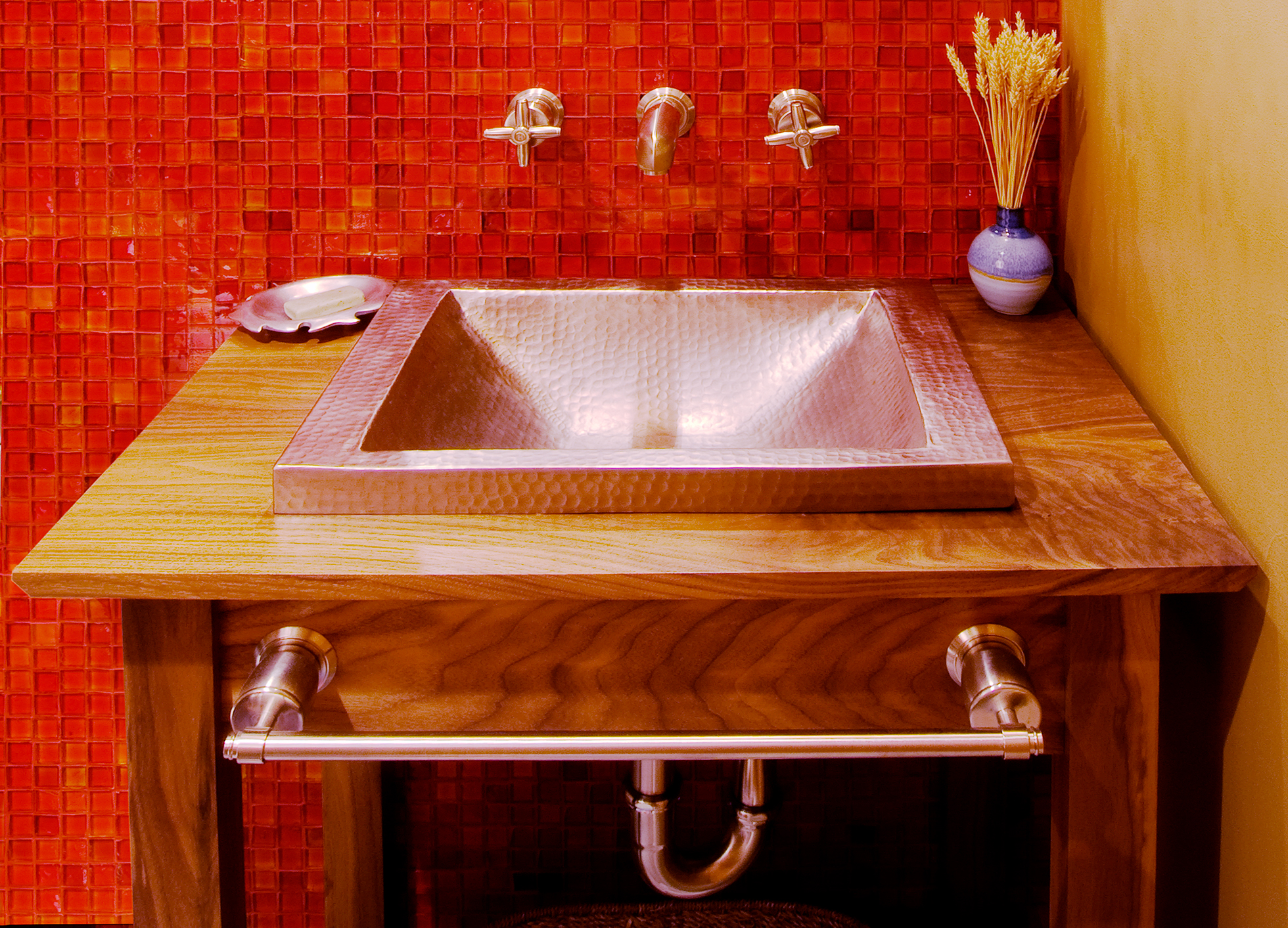 A red tiled bathroom wall with stainless sink