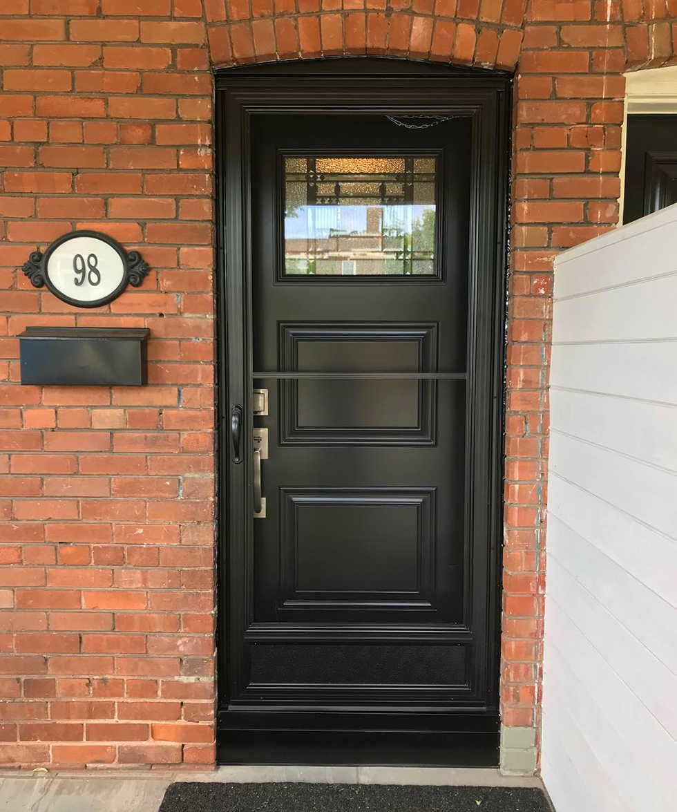 Black fiberglass front door on red brick house
