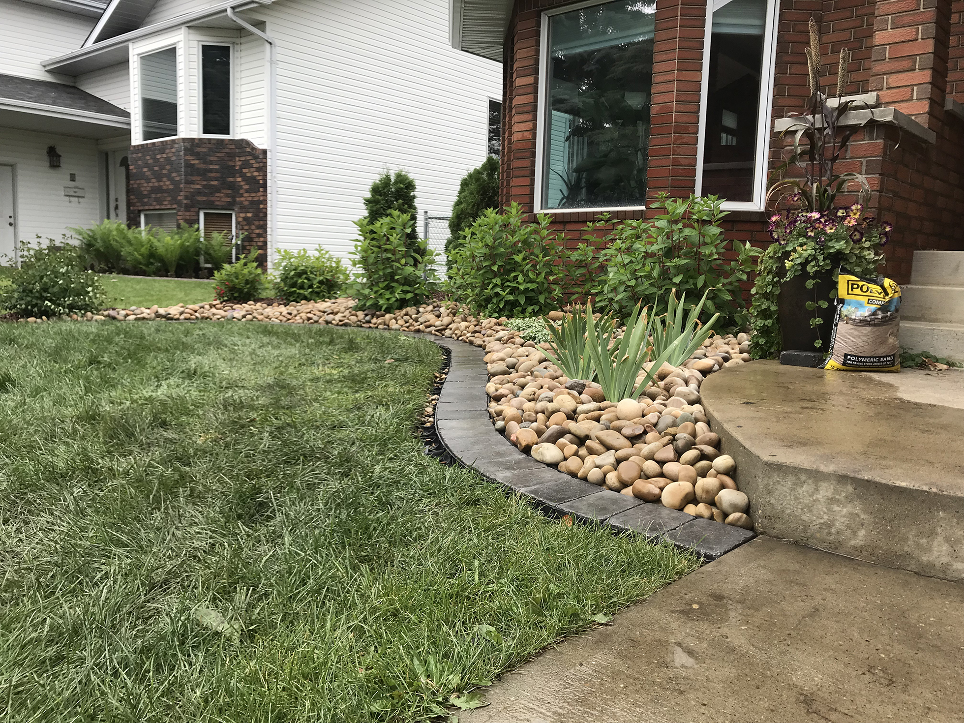 Rock edging outside red brick house | Curb Appeal Ideas
