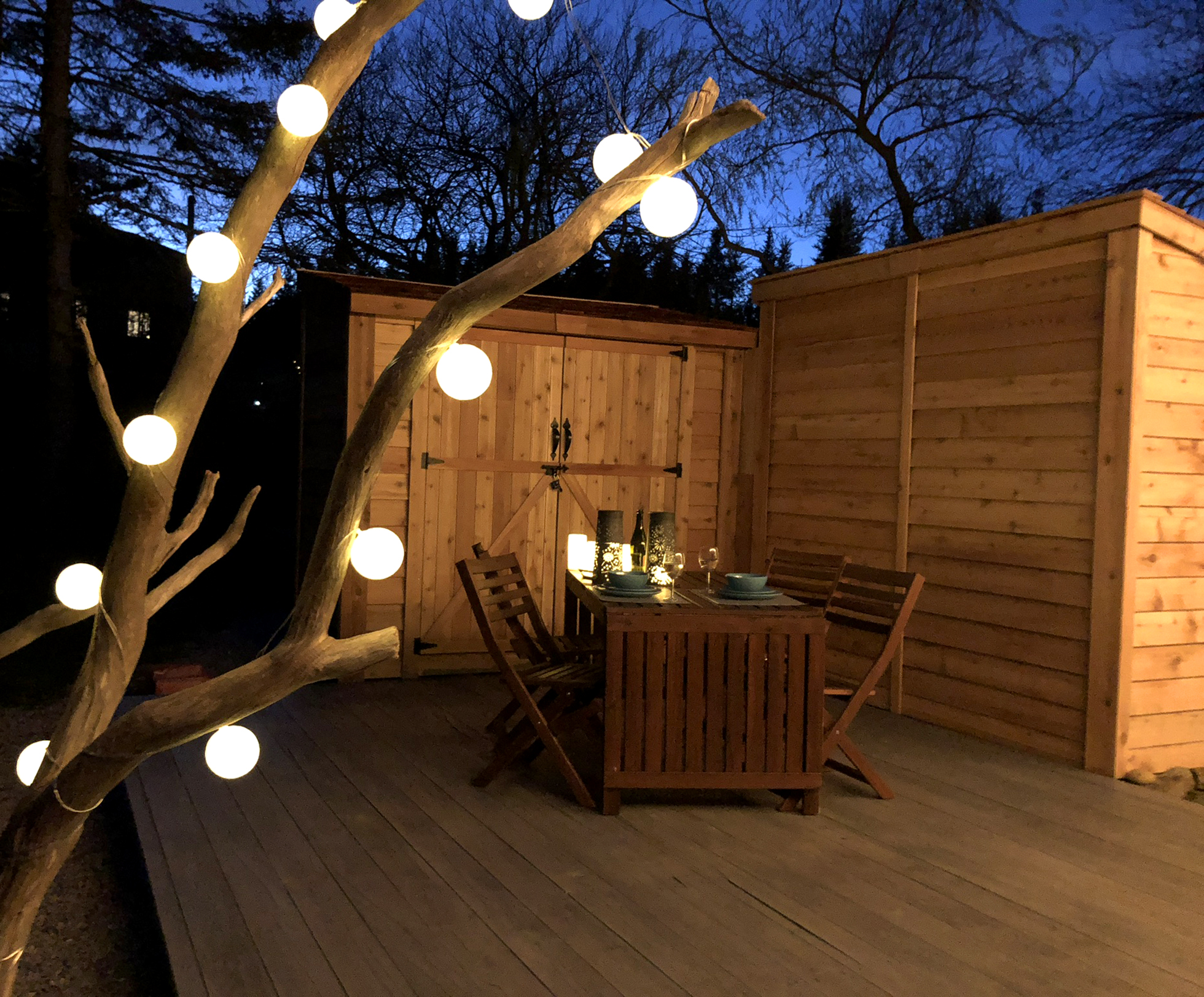 Wood deck with table illuminated by tree with globe lights