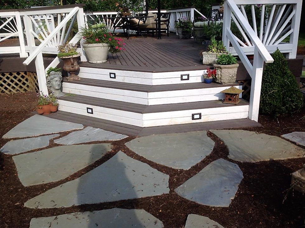 Stone pavers in mulch leading to white deck stairs