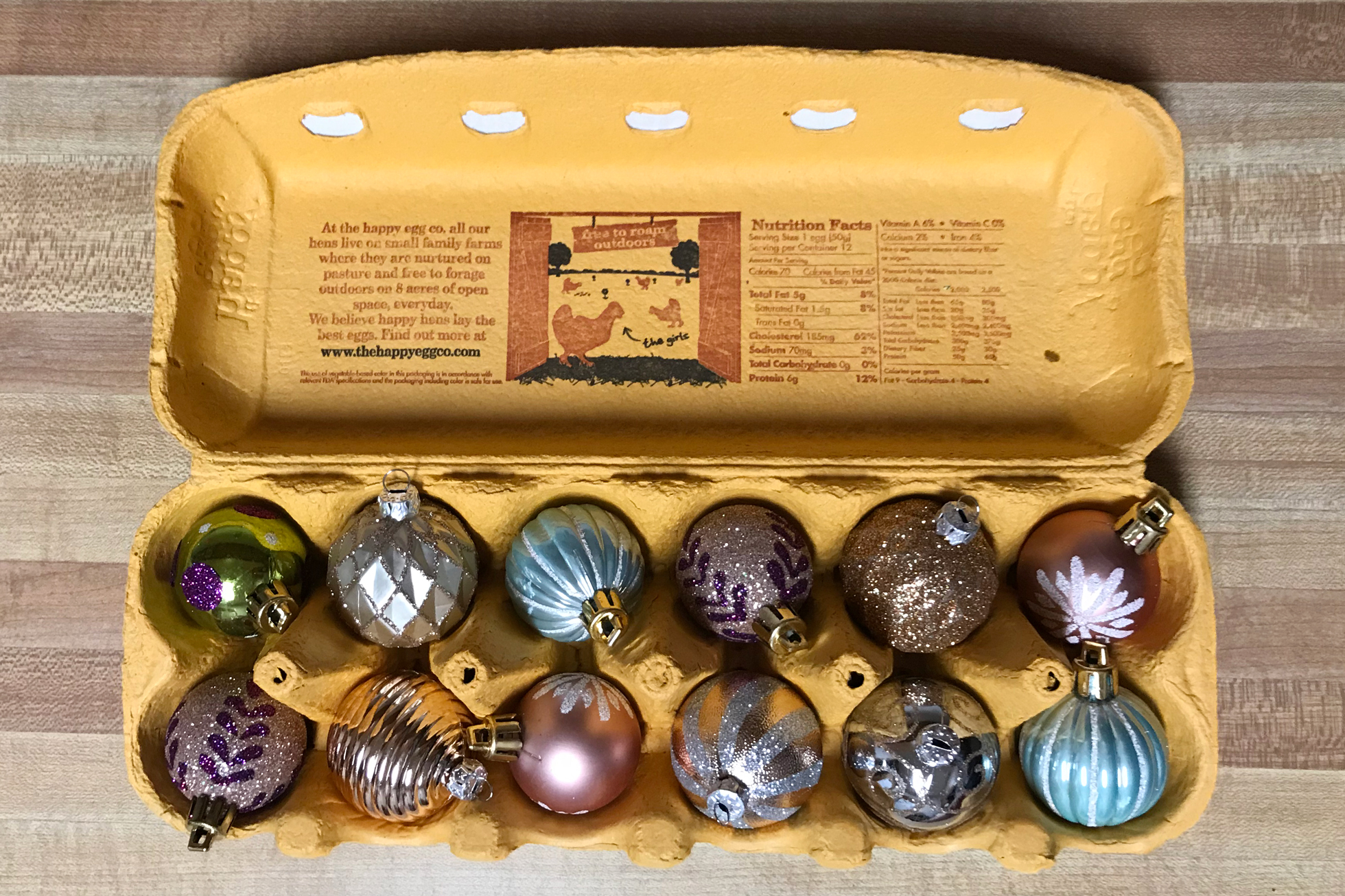Small colorful ornaments in a yellow egg carton