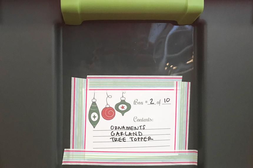 A gray Tupperware with a note of holiday supplies enclosed