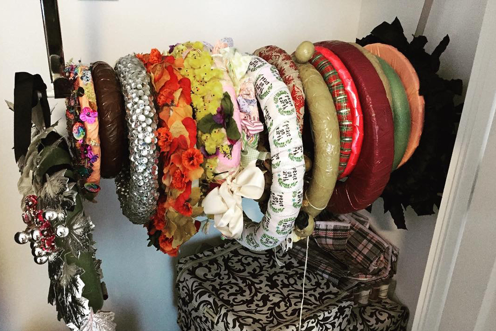 Colorful DIY wreaths hanging on a bar in a closet