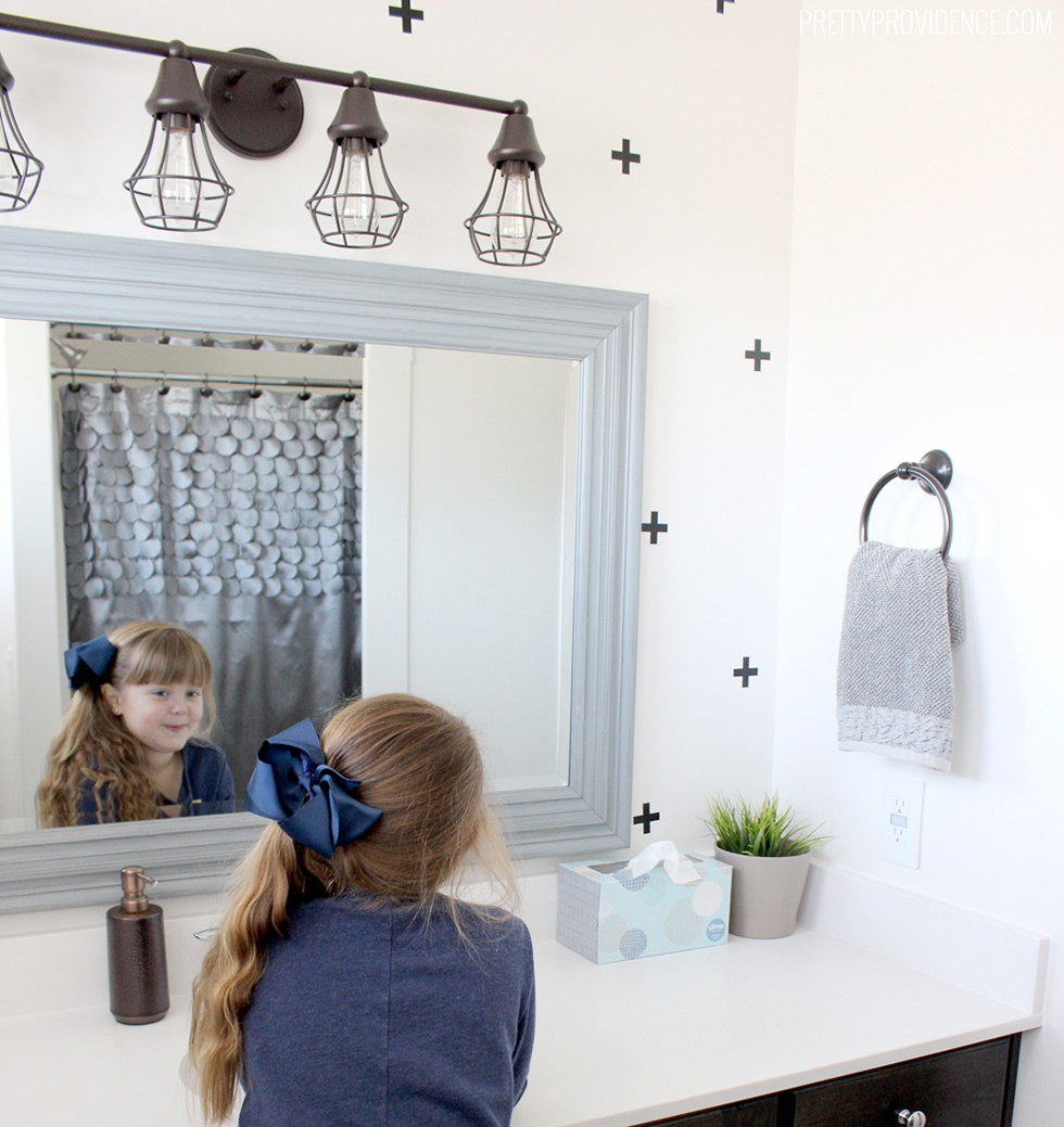 Child looking in mirror of white bathroom with black crosses
