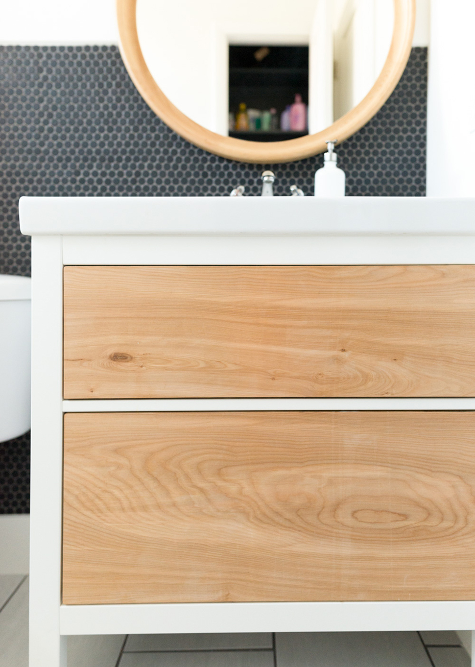 Close up of white bathroom vanity with natural wood details