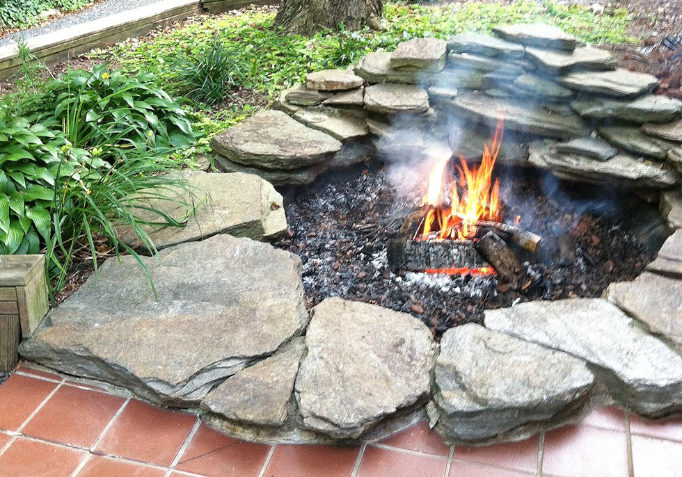 A koi pond converted into a backyard fire pit