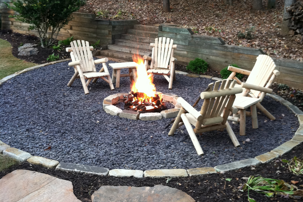 A gravel patio with fire pit, flagstone path, comfy chairs