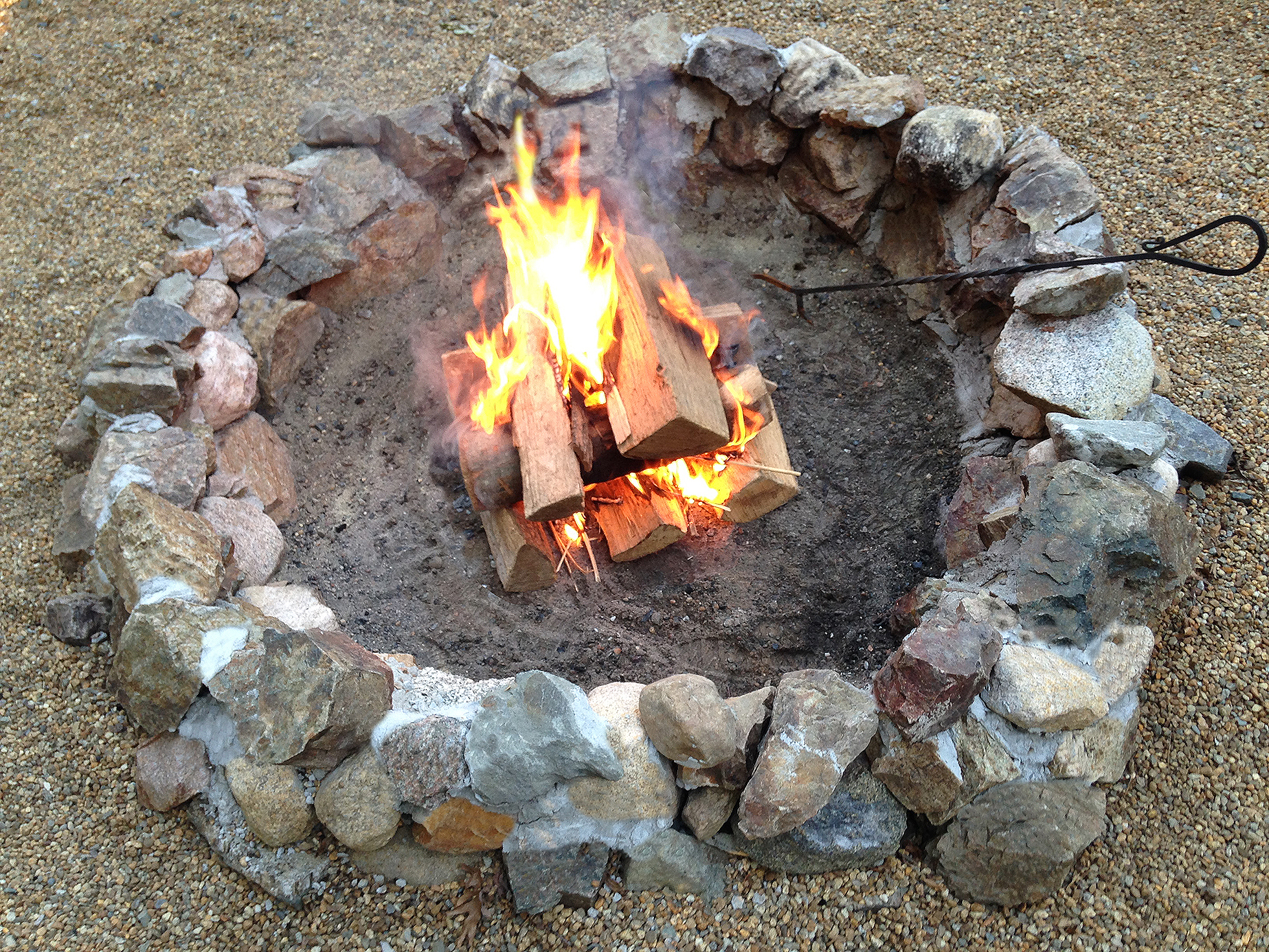 A rock fire pit with flame