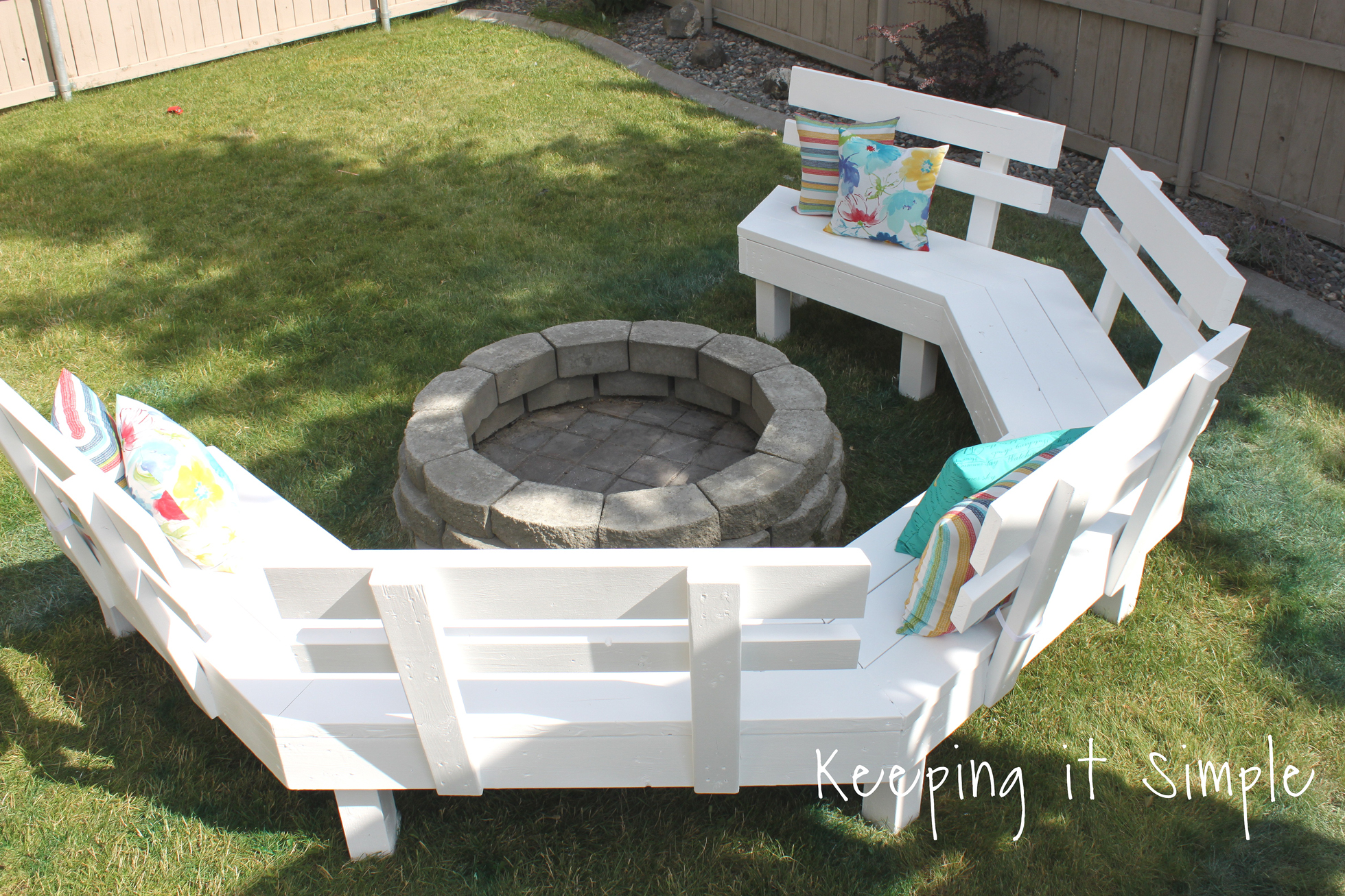 A white sofa bench surrounding a DIY paver fire pit