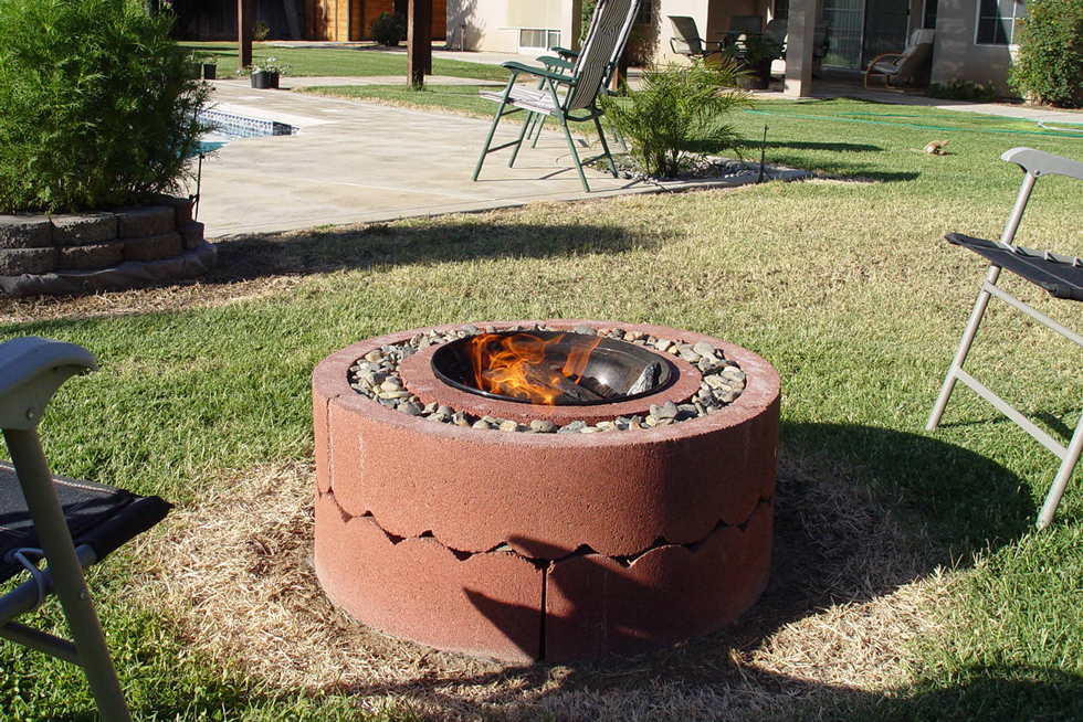 A clay-colored tree ring fire pit with flame