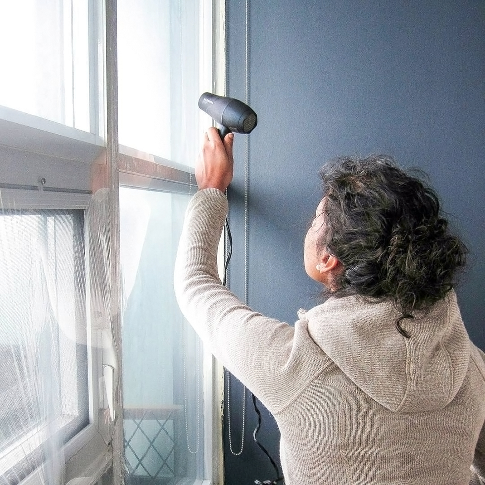 Woman using hair dryer to install insulation film on window
