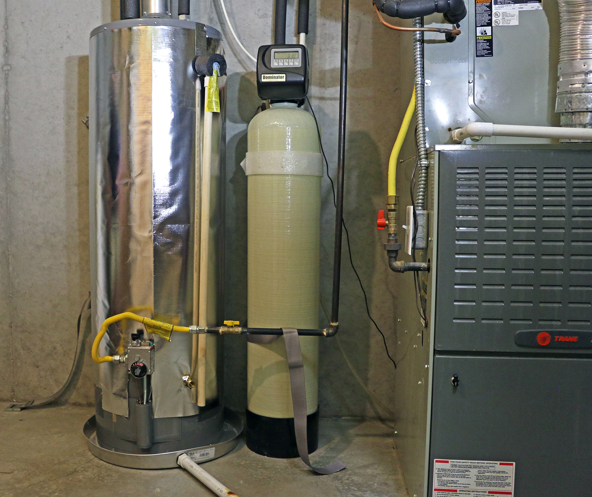 Basement water heater wrapped in silver insulation blanket