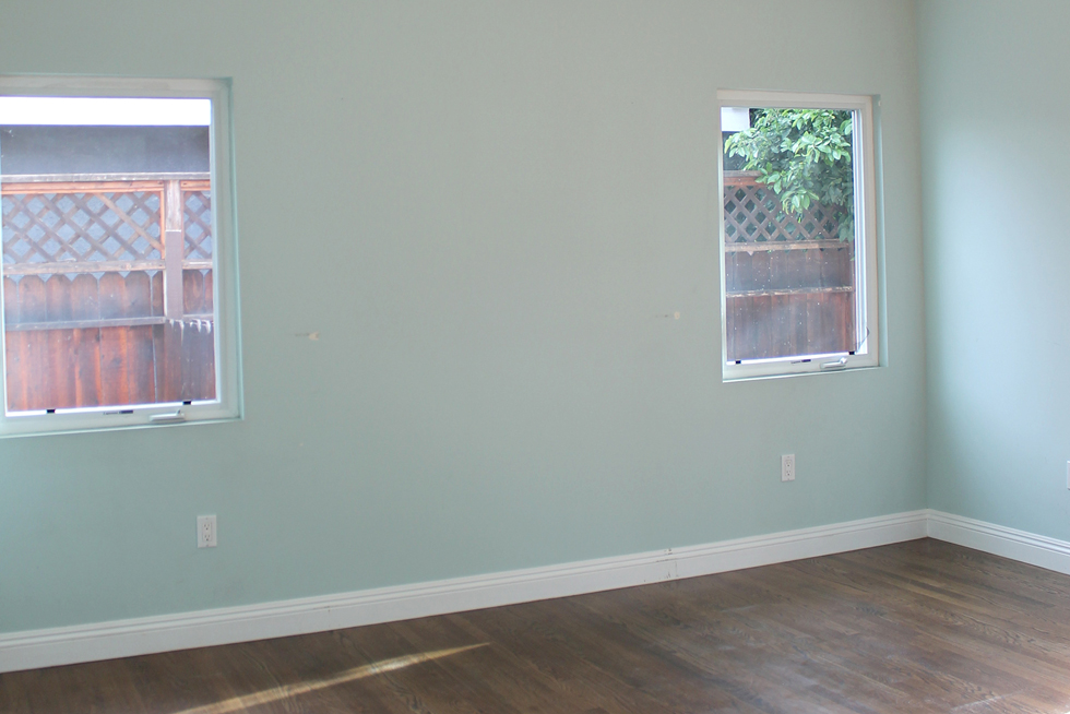 Empty bedroom with teal painted walls and dark wood floors