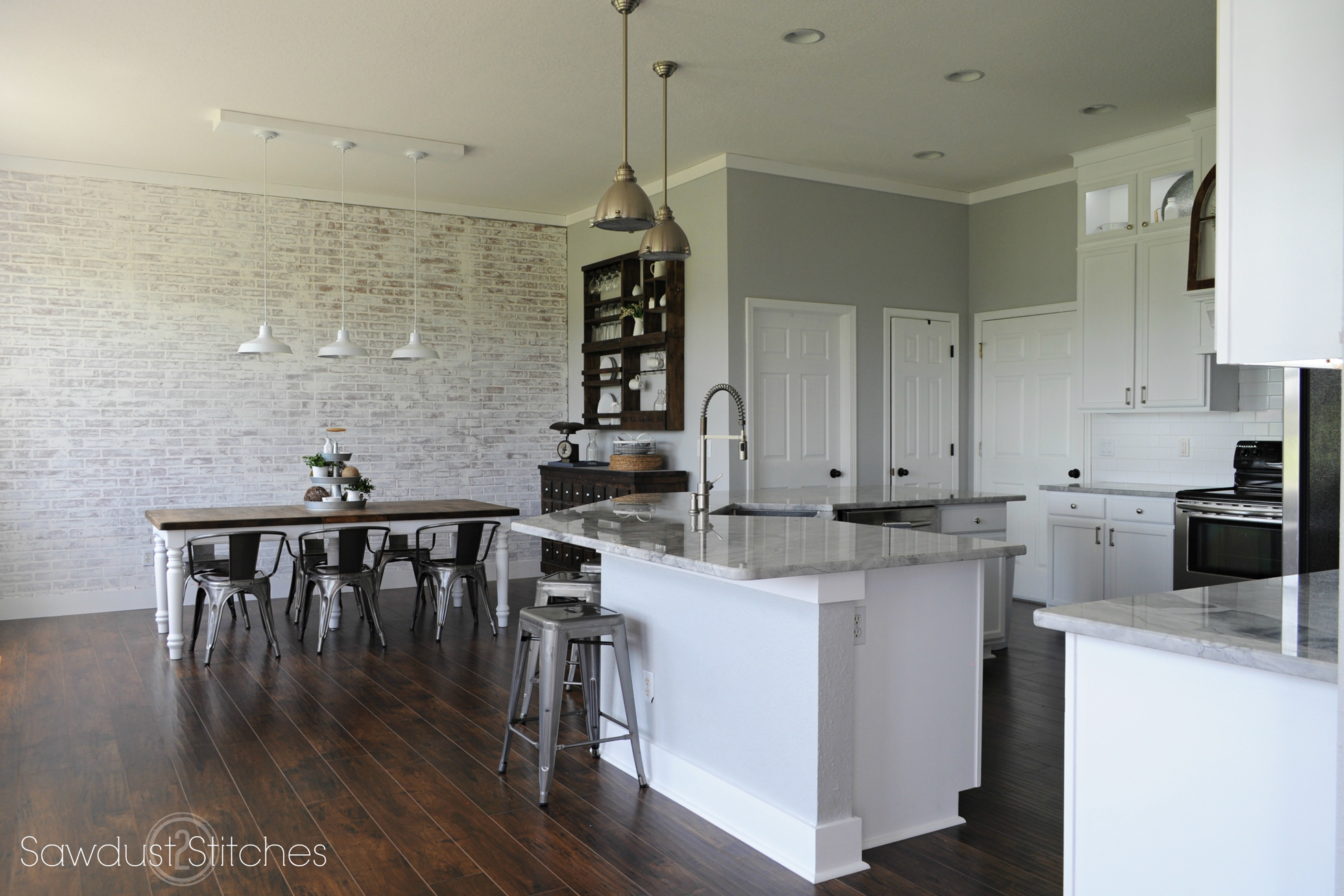 Kitchen with white cabinetry, white-washed brick wal