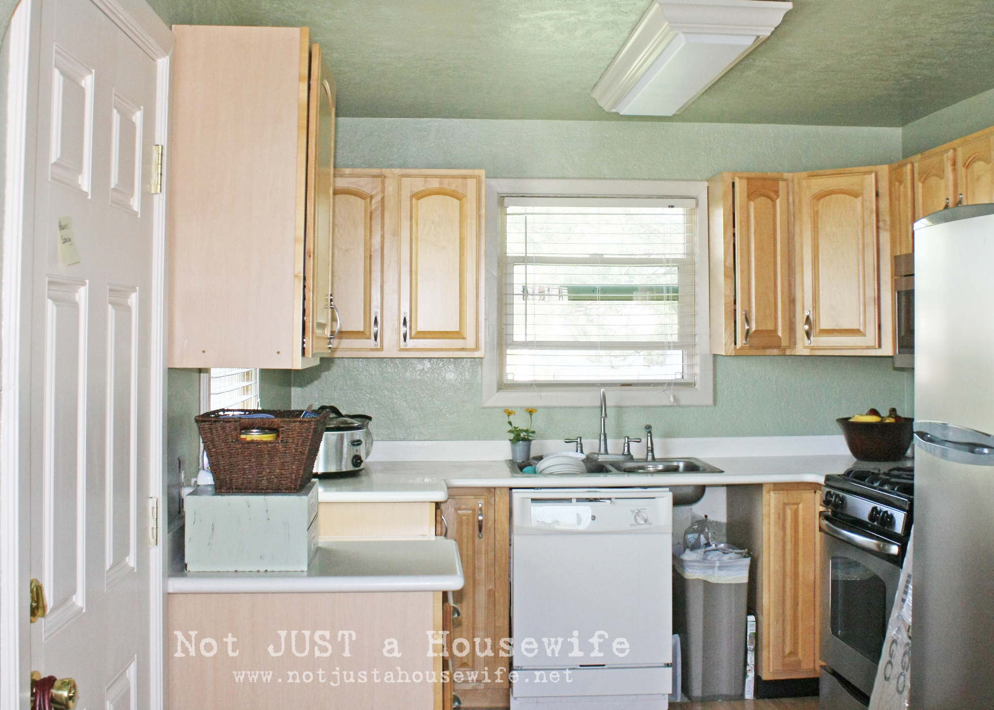 Outdated kitchen with teal walls and wood cabinetry